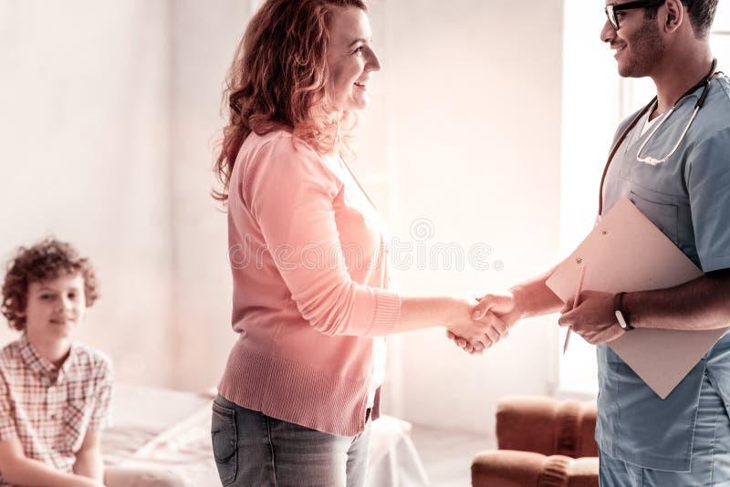 Donna riconoscente e medico che stringono le mani fotografia stock libera da diritti