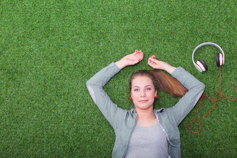 Donna rilassata che ascolta la musica con le cuffie che si trovano sull'erba fotografia stock