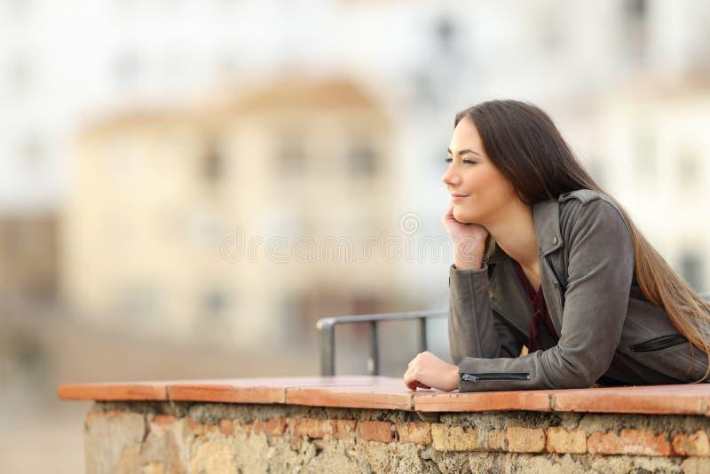 Donna rilassata che contempla le viste in un balcone fotografia stock libera da diritti
