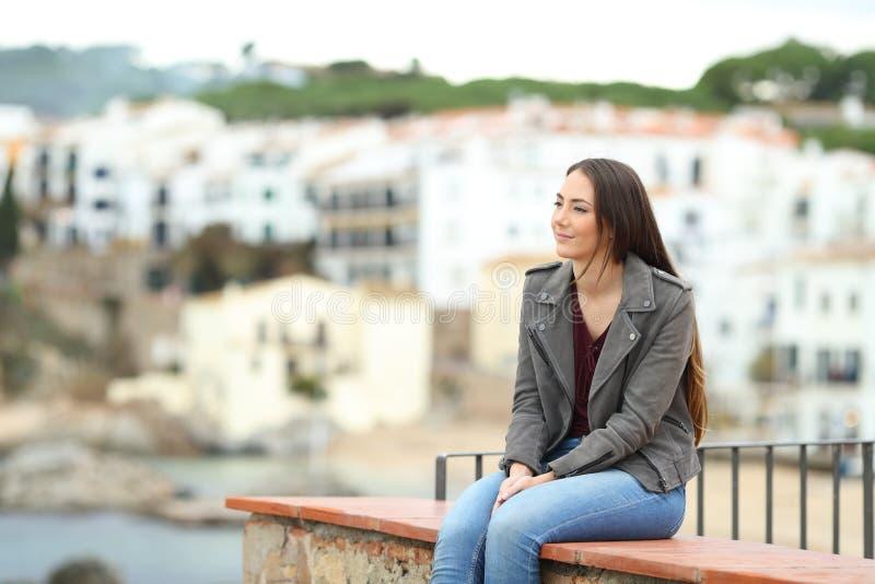 Donna rilassata che contempla le viste in una città della costa immagini stock libere da diritti