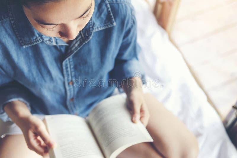 Donna rilassata che legge un libro sul letto di mattina, tempo di festa immagini stock