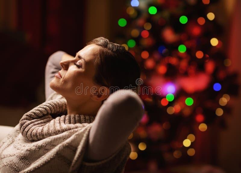 Donna rilassata che si siede in poltrona davanti all'albero di Natale fotografie stock libere da diritti