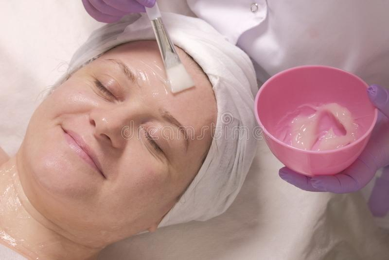 Donna rilassata con gli occhi chiusi su una procedura cosmetological Applicazione del gel nutrizionale trasparente sul fronte di  fotografia stock libera da diritti