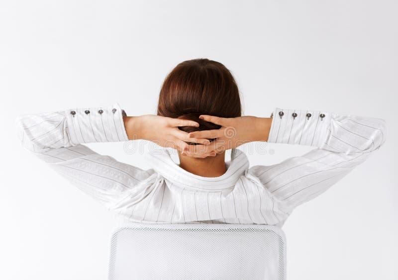 Donna rilassata dalla parte posteriore con le armi sulla testa fotografia stock
