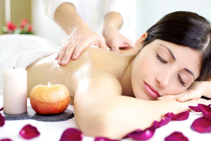 Donna rilassata felice che ottiene massaggio posteriore in stazione termale di lusso fotografia stock