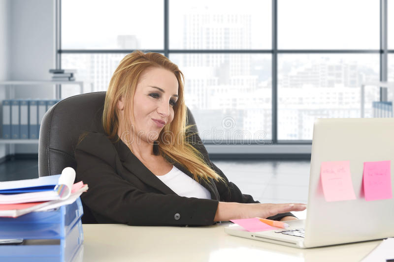 Donna rilassata 40s con seduta sicura sorridente dei capelli biondi sulla sedia dell'ufficio che lavora al computer portatile fotografia stock