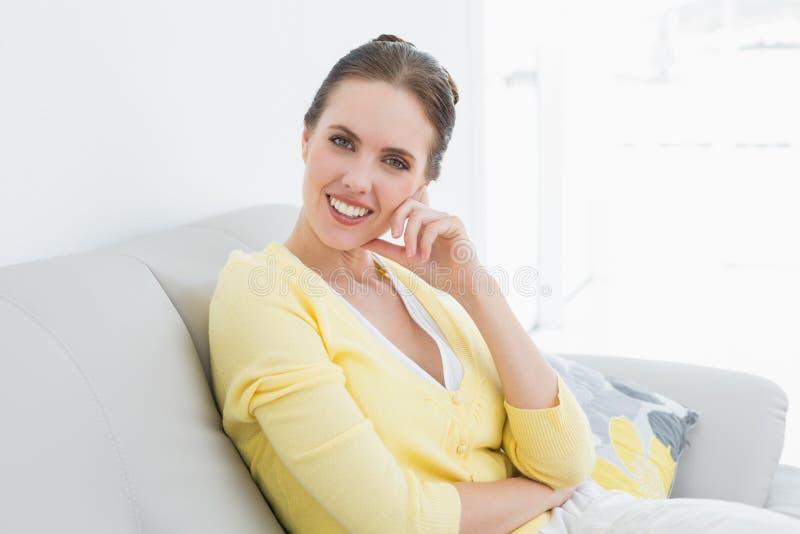Donna rilassata sorridente che si siede sul sofà a casa immagini stock