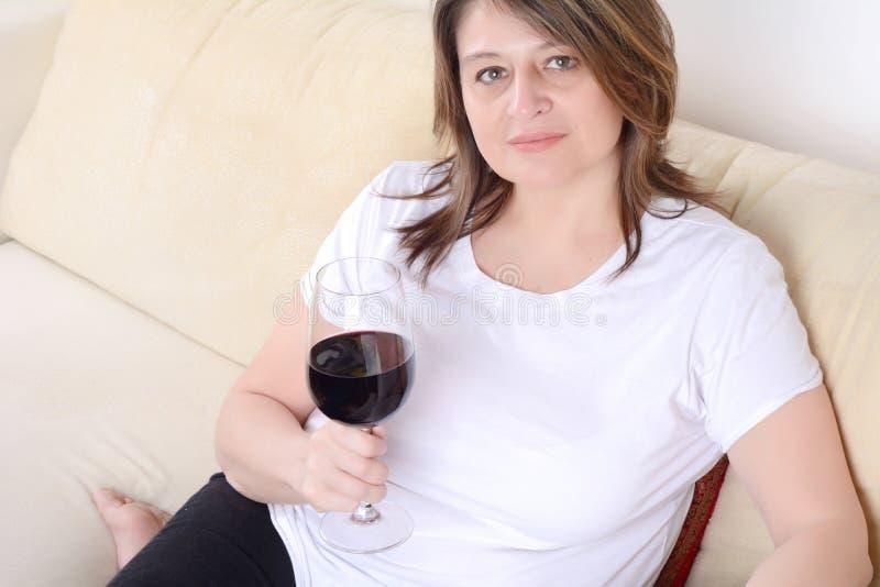 Donna rilassata sul sofà con un bicchiere di vino fotografia stock libera da diritti