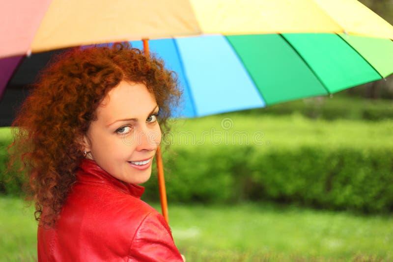 Donna in rivestimento rosso con l'ombrello multicolore fotografia stock libera da diritti