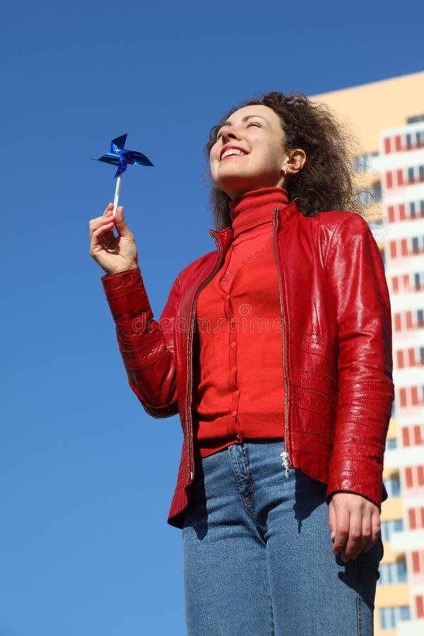 Donna in rivestimento rosso e jeans che giocano con il filatore immagini stock