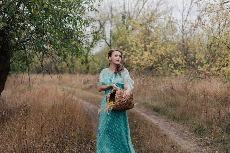 Donna romantica che porta vestito elegante lungo che sta sul campo, stagione di autunno, rilassamento in campagna, godente della  immagini stock