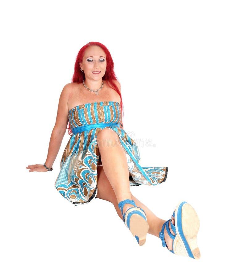 Donna rossa dei capelli che si siede sul pavimento immagine stock libera da diritti