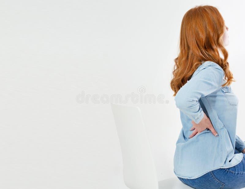 Donna rossa dei capelli con dolore alla schiena isolata su bianco fotografie stock