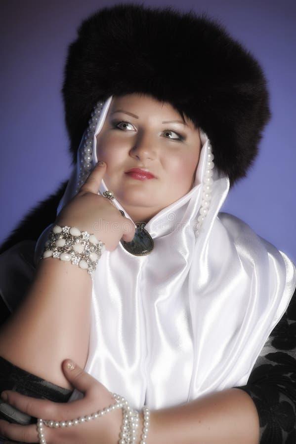Donna russa in un cappello di pelliccia, in una sciarpa bianca e con le perle immagine stock
