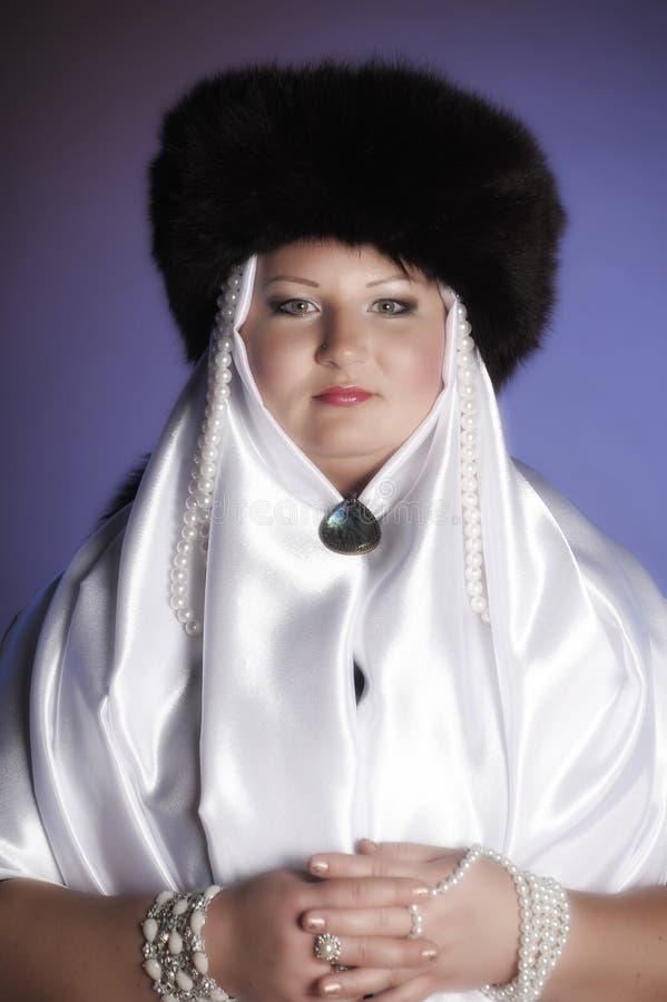 Donna russa in un cappello di pelliccia, in una sciarpa bianca e con le perle fotografia stock