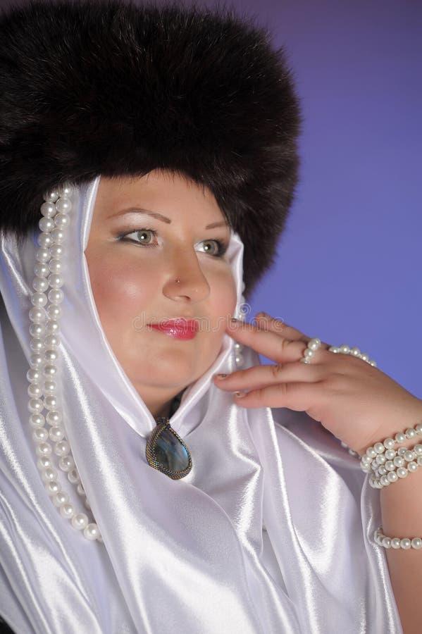 Donna russa in un cappello di pelliccia, in una sciarpa bianca e con le perle fotografie stock