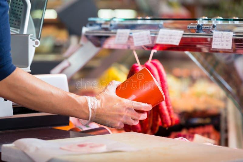Donna in salsiccia della tenuta di macelleria in sue mani da vendere immagine stock libera da diritti