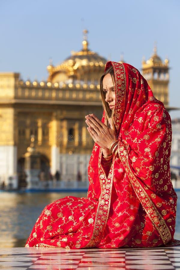 Donna in sari rossi che prega al tempiale dorato. fotografia stock