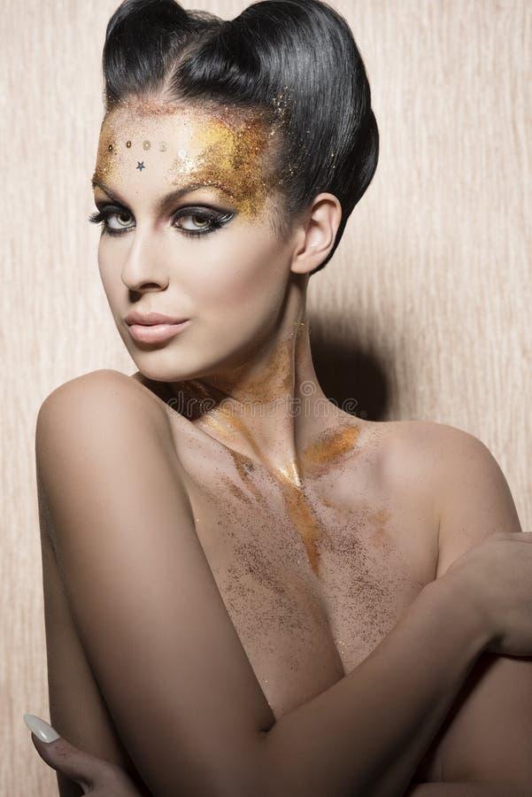 Donna sbalorditiva con trucco dorato di lusso immagine stock