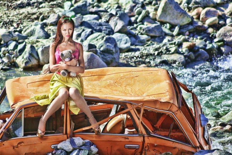 Donna in scaletta della bamboletta che si siede su un'automobile rotta al sole con l'orsacchiotto a disposizione fotografie stock libere da diritti
