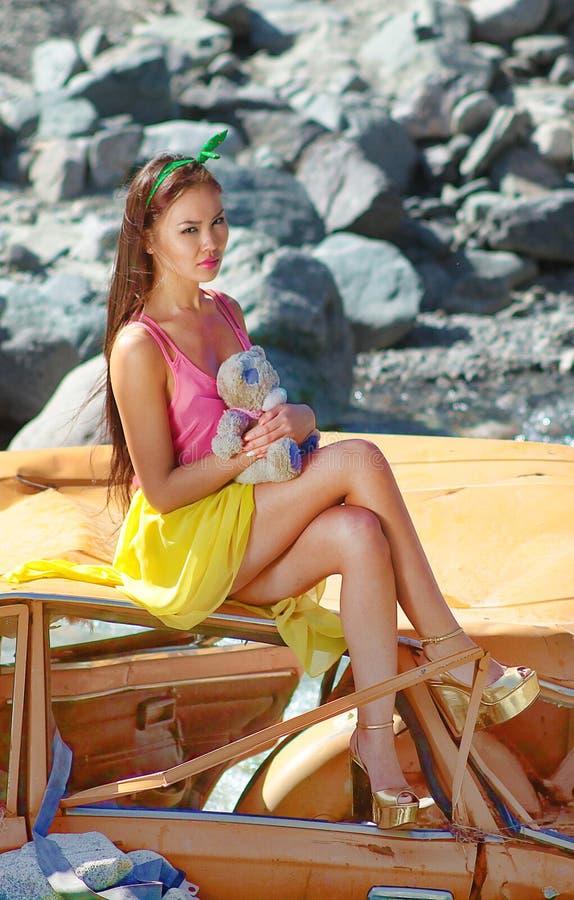 Donna in scaletta della bamboletta che si siede su un'automobile rotta al sole con l'orsacchiotto a disposizione fotografie stock