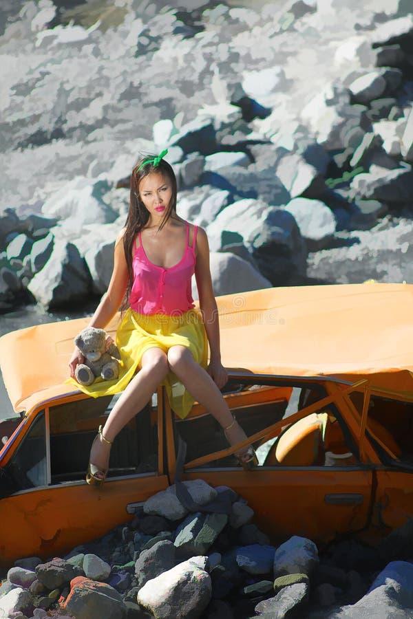 Donna in scaletta della bamboletta che si siede su un'automobile rotta al sole con l'orsacchiotto a disposizione fotografia stock libera da diritti