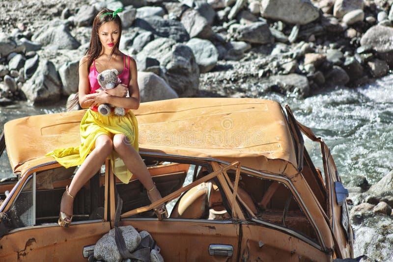 Donna in scaletta della bamboletta che si siede su un'automobile rotta al sole con l'orsacchiotto a disposizione immagine stock