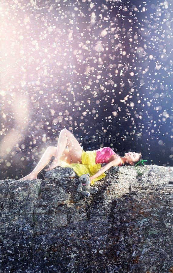 Donna in scaletta della bamboletta che si trova su una pietra al sole con l'orsacchiotto a disposizione immagine stock libera da diritti
