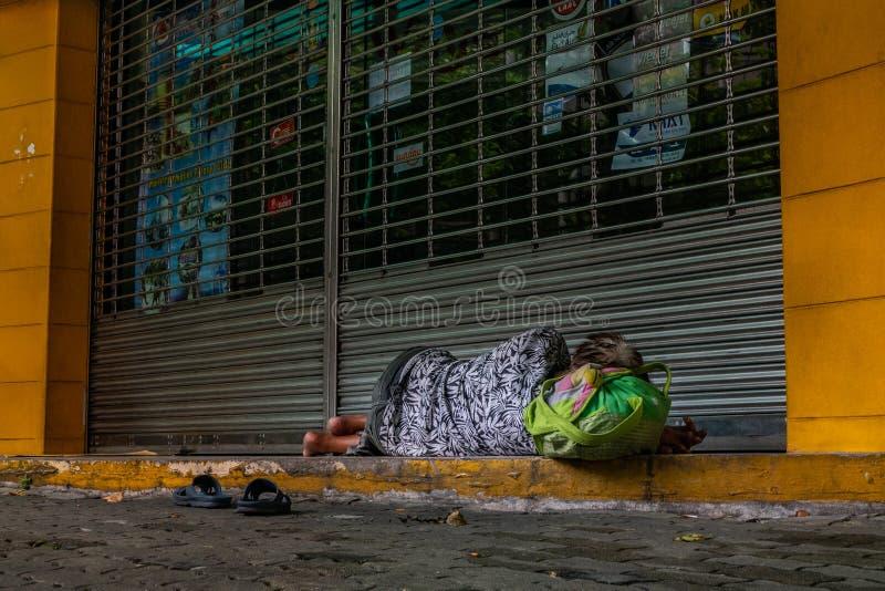 Donna scalza senza tetto che dorme sul marciapiede davanti alla porta del negozio chiuso, edizione sociale fotografia stock libera da diritti