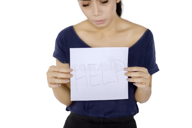 Donna scarna che tiene una carta con la parola di aiuto fotografia stock