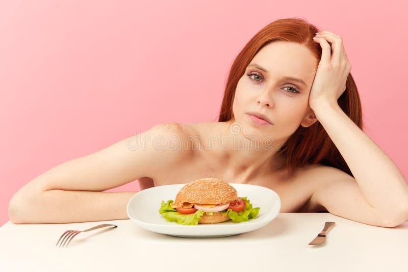 Donna scarna dai capelli rossi con gli occhi avidi che sono hamburger pronto da mangiare fotografia stock