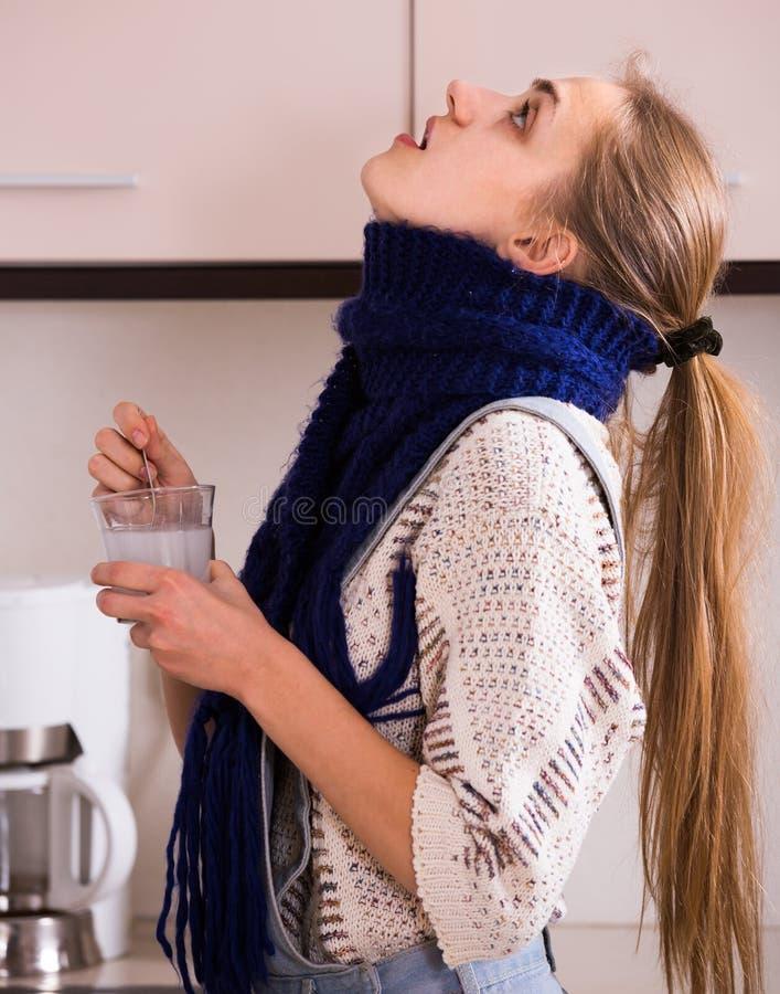 Donna in sciarpa che fa i gargarismi gola con soda domestica immagini stock libere da diritti
