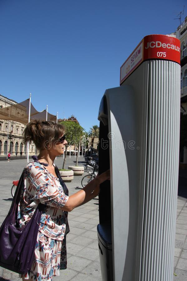 Donna sconosciuta alla macchina del biglietto per le bici municipali immagini stock libere da diritti