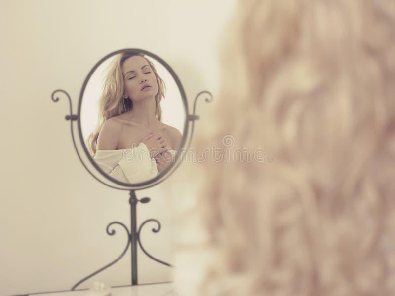 Donna seducente nello specchio fotografia stock