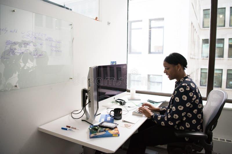 Donna seduta davanti al monitor del computer fotografie stock libere da diritti