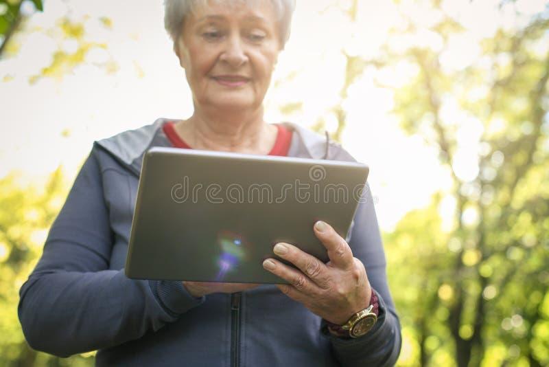 Donna senior in abbigliamento di sport dopo l'esercizio facendo uso dei Di fotografia stock libera da diritti