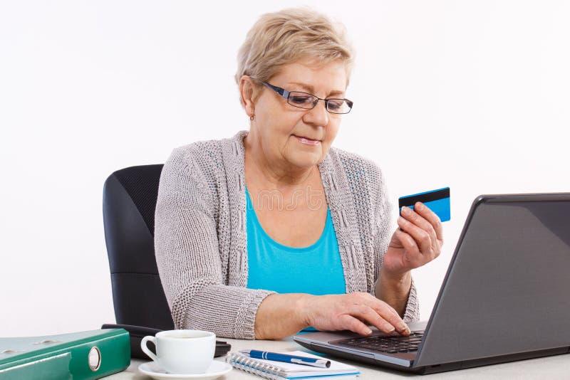 Donna senior anziana con la carta di credito e computer portatile che paga sopra Internet le fatture pratiche o l'acquisto online fotografie stock