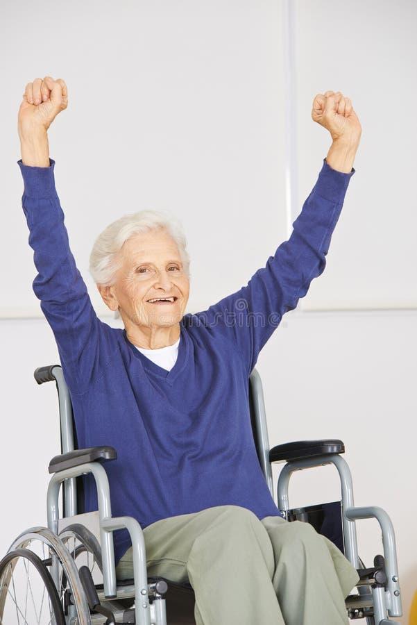 Donna senior anziana nell'incoraggiare della sedia a rotelle immagini stock libere da diritti