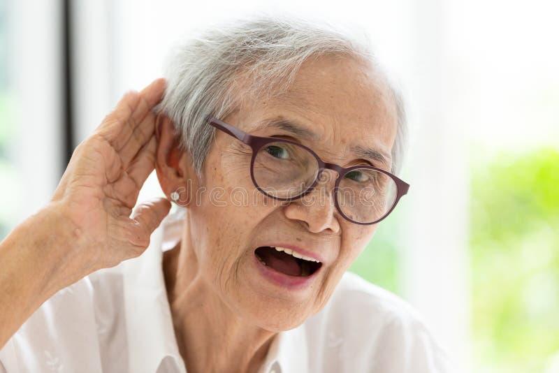 Donna senior asiatica che ascolta duro dai hand's fino all'orecchio, incontrando difficoltà nell'udienza, donna anziana sentire fotografie stock