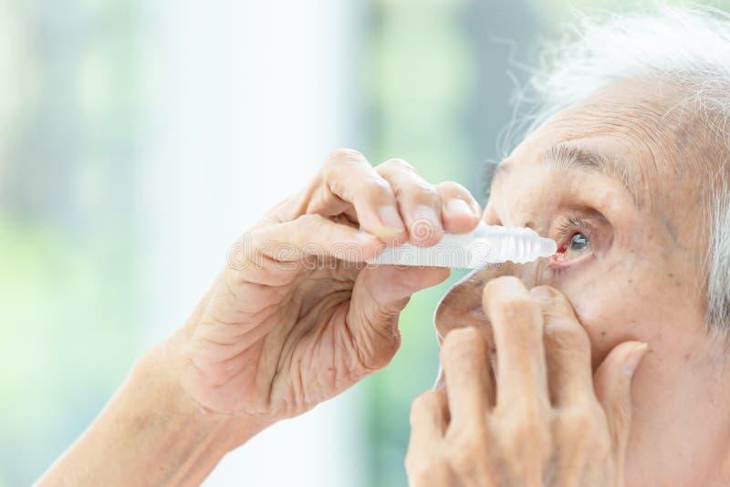 Donna senior asiatica che mette collirio, punto di vista del primo piano della persona anziana che utilizza bottiglia del colliri fotografia stock