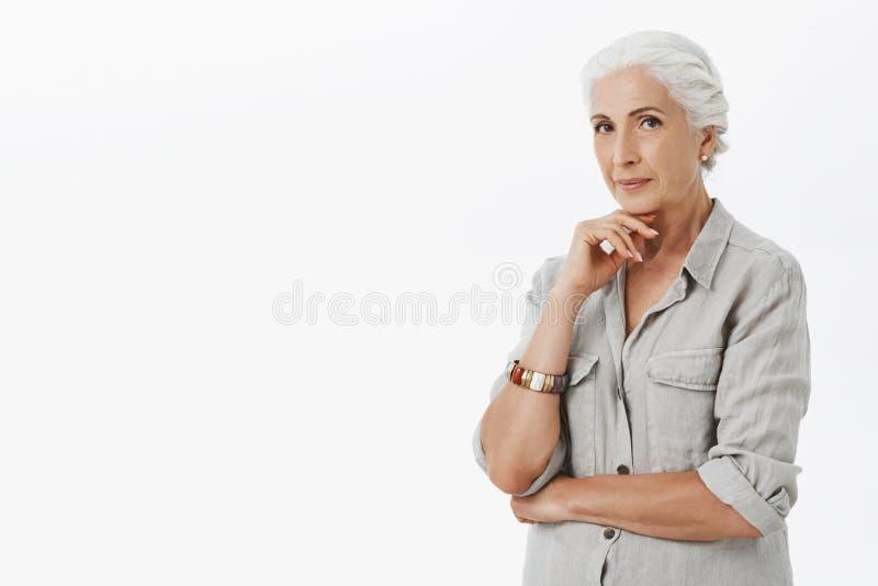 Donna senior astuta affascinante e creativa che crea le nuove idee per l'affare futuro per non volere ritirarsi tenuta della mano fotografia stock libera da diritti