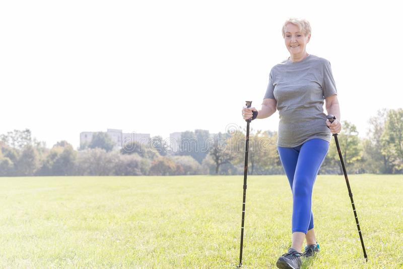 Donna senior attiva con i pali di trekking che cammina nel parco fotografie stock