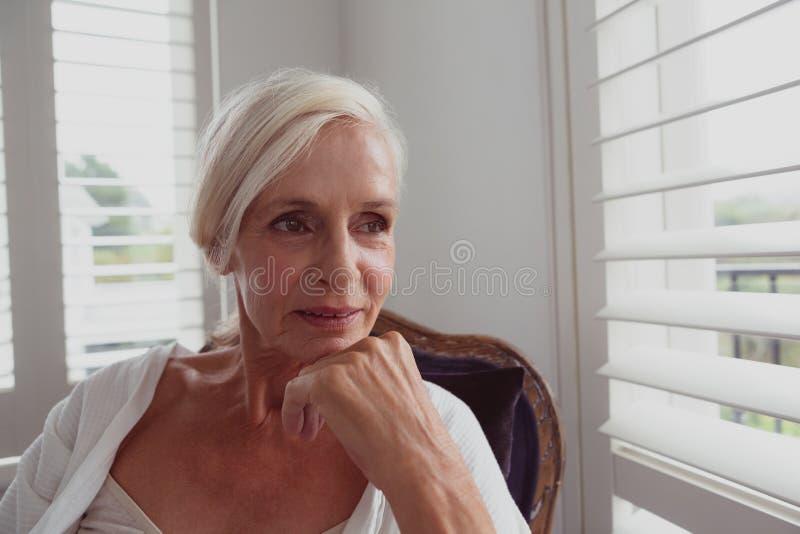 Donna senior attiva con la mano sul mento che si siede sulla sedia in una casa comoda fotografia stock libera da diritti