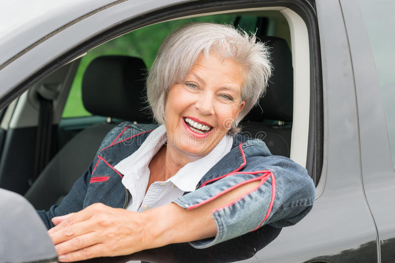 Donna senior in automobile immagine stock