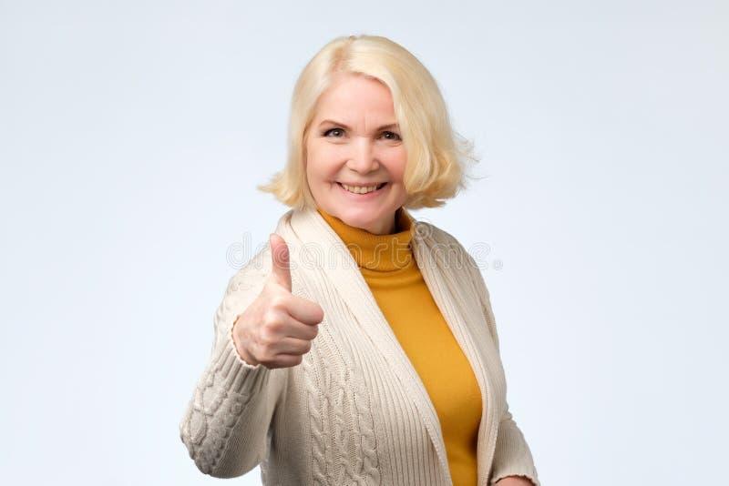 Donna senior bionda felice che mostra i pollici su fotografia stock