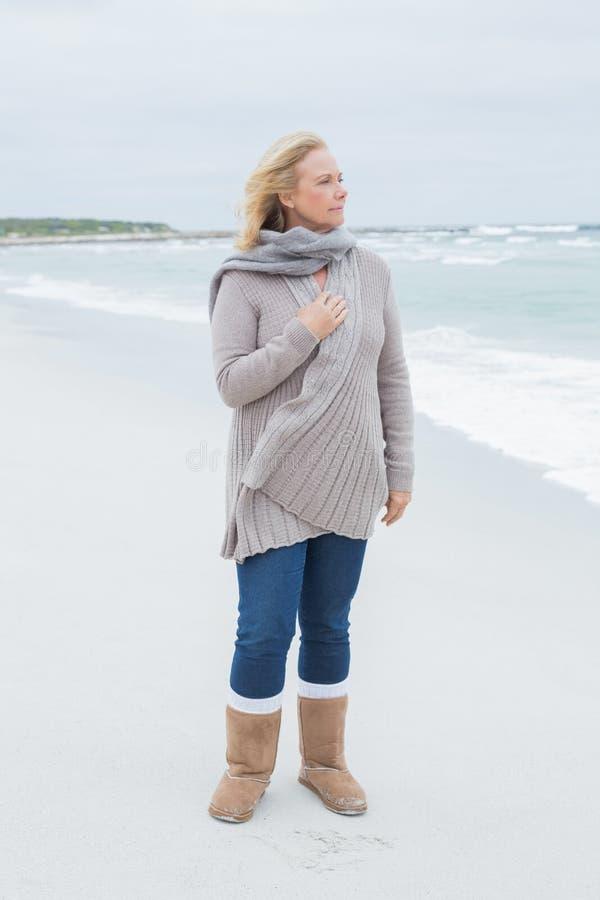 Donna senior casuale contemplativa alla spiaggia immagine stock
