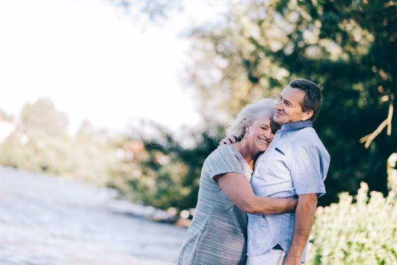 Donna senior che abbraccia il suo marito immagini stock libere da diritti