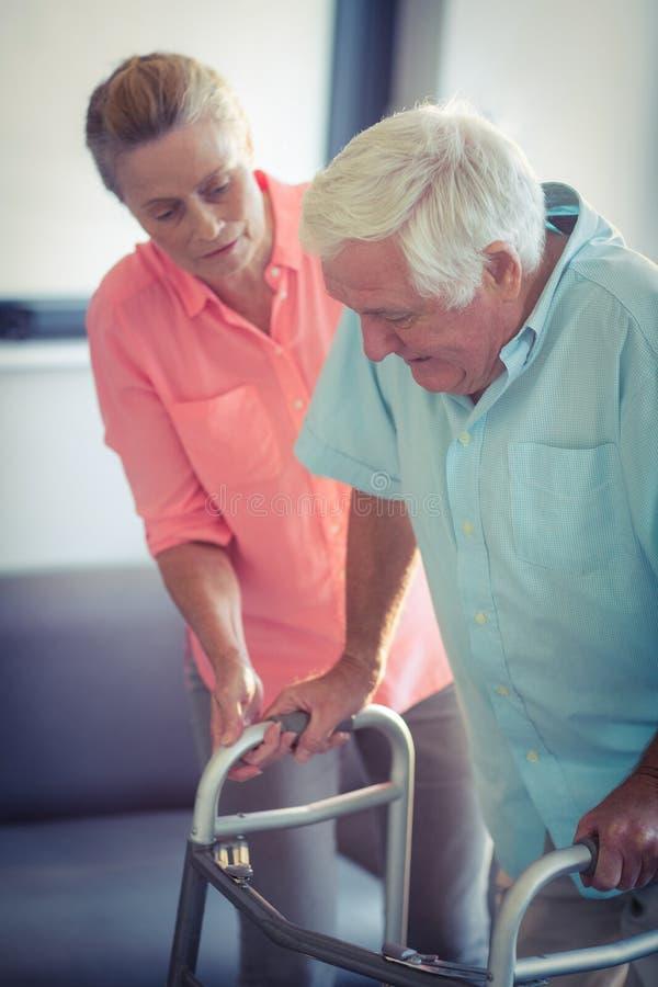 Donna senior che aiuta uomo senior a camminare con il camminatore immagine stock