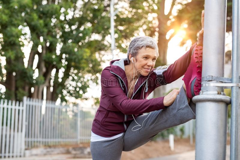 Donna senior che allunga le gambe all'aperto immagine stock libera da diritti