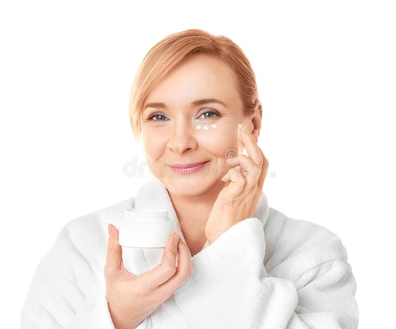 Donna senior che applica crema antinvecchiamento sul fronte immagini stock libere da diritti